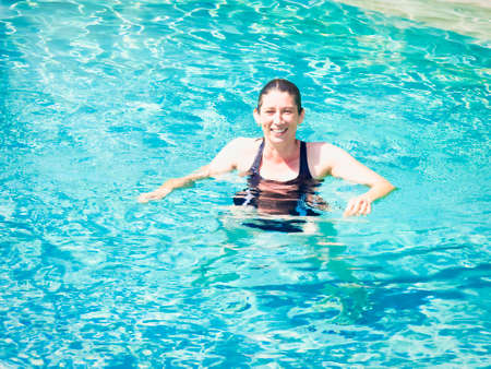 Cheerful mature woman relaxing in swimming-pool in crystal water with summer light Banque d'images