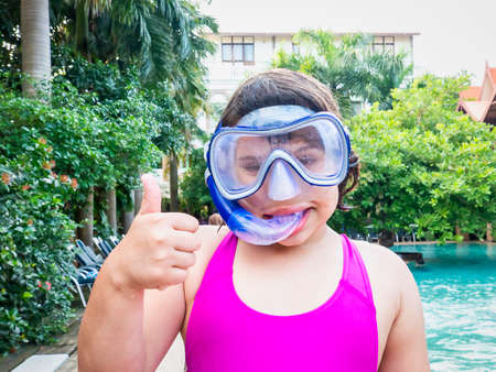 Beach vacation fun girl wearing a snorkel scuba mask making a goofy face while swimming in ocean water. Closeup portrait of caucasian girl on her travel holidays. Summer or winter destination.