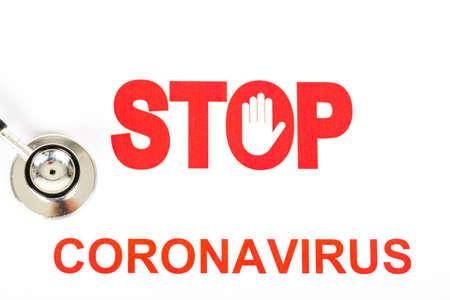 Text phrase Coronavirus with red letters with STOP sign on white background. Copy space. With stethoscope