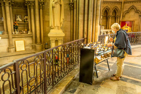 BAYEUX, FRANCE - SEPTEMBER Circa, 2020. Unidentified senior woman lights a prayer candle at the celebration of end of lockdown by the church of Notre Dame at Bayeux, France. Wearing face mask for coronavirus prevention Editoriali