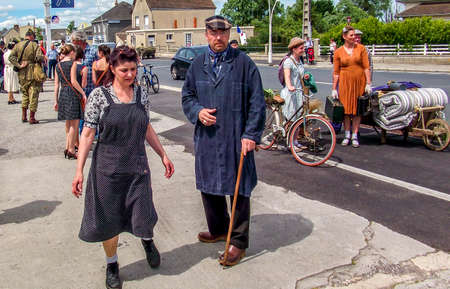 SAINTE MERE L'EGLISE, FRANCE - JUNE 6, 2019. Parade of People dressed up in 1940's clothing posing in front of a World War 2, D-Day ceremony in Normandy. People found liberty after 5 years war. Happy day memorial