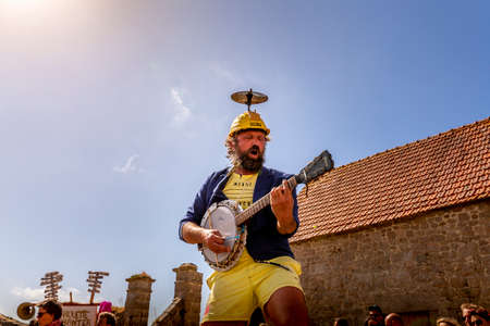 VALOGNES, FRANCE - SEPTEMBER Circa, 2020. Unidentified street musicians and performers singing and dancing outdoors. Very funny show with happy spectator. Traditional french music on public event.