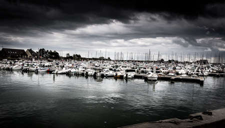 SAINT VAAST, FRANCE - SEPTEMBER Circa, 2020. Dramatic cloudy Sky landscape on the harbor with sailboats. Panorama, dark pessimist atmosphere feelings. Desaturated image Editorial