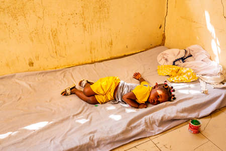 MBOUR, SENEGAL - DECEMBER Circa, 2020. Cute poor african little child girl on dirty sheets lying in bed with sad moody at home. Yellow wall and yellow child cloths.