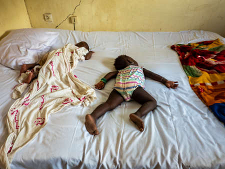 MBOUR, SENEGAL - DECEMBER Circa, 2020. Two African little infant and baby wearing diaper and sleeping on bed with comfort. On dirthy white bed, poverty in Africa Editorial