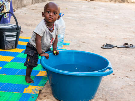 MBOUR, SENEGAL - DECEMBER Circa, 2020. African baby, less than one year, wanting bathing in a basin in a poor village senegalese house. Turning around big blue bowl to play with water.