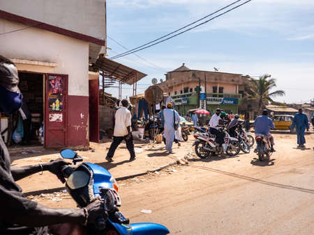 MBOUR, SENEGAL - DECEMBER Circa, 2021. Few women and men with  Virus mask walking, driving in street village. Some wearing mask, some does not. Senegalese people refuse reality of covid 19 in their country. Editorial