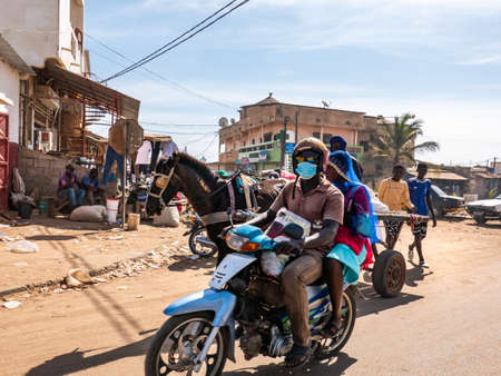 MBOUR, SENEGAL - DECEMBER Circa, 2021. Few women and men with   Virus mask walking, driving in street village. Some wearing mask, some does not. Senegalese people refuse reality of covid 19 in their country.