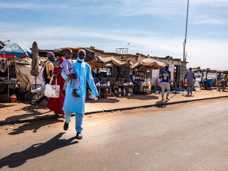 MBOUR, SENEGAL - DECEMBER Circa, 2021. Few women and men with  Virus mask walking in street village market. Some wearing mask, some does not. Senegalese people refuse reality of covid 19 in their country.
