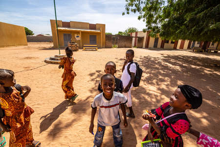 MBOUR, SENEGAL - DECEMBER Circa, 2020. Group of unidentified teenagers standing up in playground of the school, outdoors on a sunny summer day. Happy to get new bags given by international ngo. Poor rural children. 新闻类图片