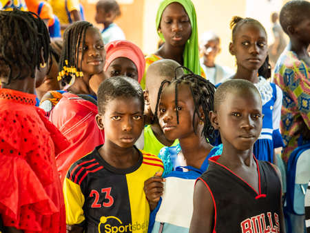 MBOUR, SENEGAL - DECEMBER Circa, 2020. Group of unidentified teenagers standing up in playground of the school, outdoors on a sunny summer day. Waiting for new bags given by international ngo. Poor rural children. 新闻类图片