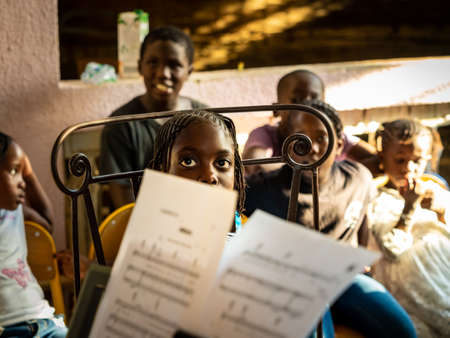 MBOUR, SENEGAL - DECEMBER, Circa, 2020. Unidentified group of cheerful children sitting on chairs outdoors, looking at teacher to learn song with musicans. Sunny day, selective focus.