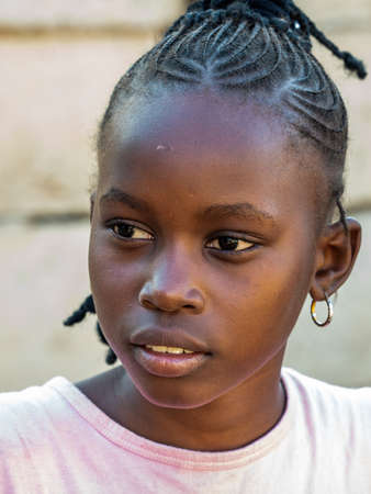 MBOUR, SENEGAL - JANUARY Circa, 2021. Portrait of unidentified young senegalese children, not looking at camera. Beautiful skin, hairs, light. outdoors