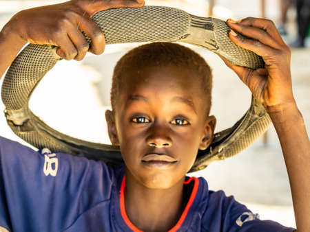MBOUR, SENEGAL - JANUARY Circa, 2021. Portrait of unidentified young senegalese child with rubber wheel on head, looking at camera. Happy feeling and poverty. outdoors 新闻类图片