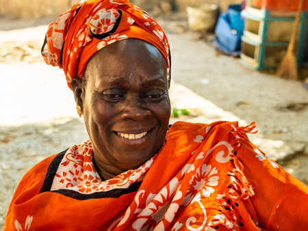MBOUR, SENEGAL - JANUARY Circa, 2021. Unidentified senegalese pretty mature woman in traditional dress outdoor looking up smiling. Poverty and happiness in village