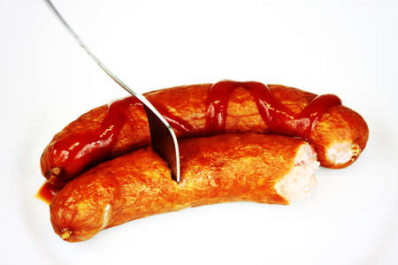 Two ham sausages with ketchup on white background