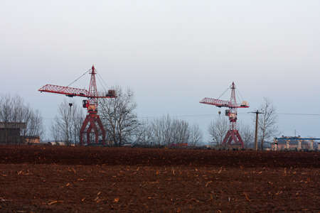 Two construction cranes next to field Stock Photo