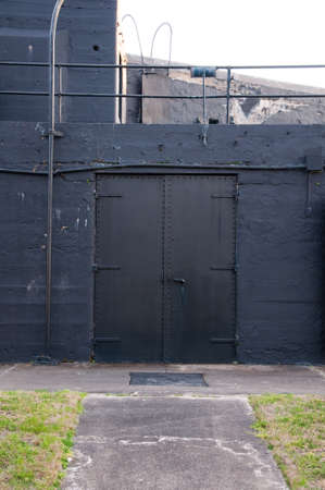 A double doorway entrance into a historic fort near Charleston, South Carolina  Includes a large metal door on a black background
