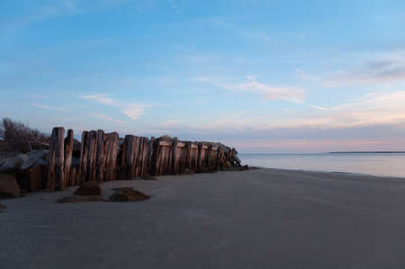 sc: Weathered wooden fence barrier and rocks protecting the coastline during sunset. Near Charleston, South Carolina. Stock Photo