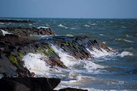 Waves crashing into a rocky shoreline near high tide, known to be a deadly current area  photo