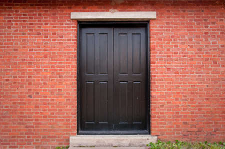 Black door on a brick building exterior with concrete stairs underneath  Taken near Historic Charleston, South Carolina Stock Photo - 12895646