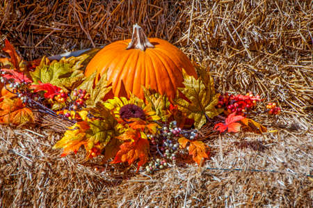 A seasonal autumn display with hay, pumpkins and other seasonal items Stock Photo
