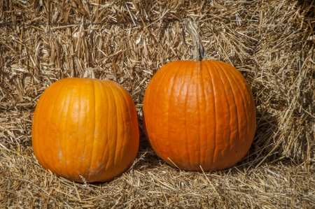 A pair of pumpkins on a bay of hay Stock Photo