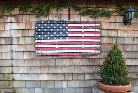 A vintage wooden flag attached to the side of a building with a small potted pine tree covered in holiday lights