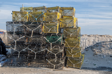 Lobster traps piled high at the shore waiting to be loaded onto a fishing vessel Stock Photo