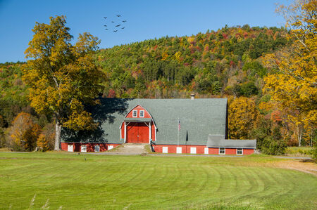 A large well maintained barn with a mountain of foliage in the background