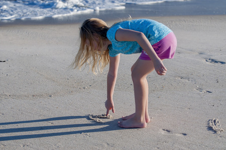 A young girl drawing in the sand at the beach Stock Photo