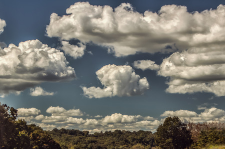 puffy: Puffy cumulus clouds over the land. Stock Photo