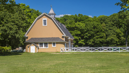 Butterscotch colored dairy barn in Hecksher Park, NY. Stock Photo - 115341515