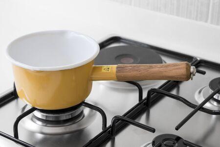 gas stove: Yellow pot on a gas stove