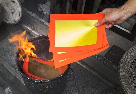 burning money: Burning of Chinese Offering Paper used by the Chinese in religious worship Stock Photo