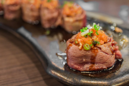 battleship: Select focus of beef sushi gunkan maki with salmon paste topping ready to serve in Select focus of beef sushi gunkan maki with salmon paste topping ready to serve in luxury  restaurant