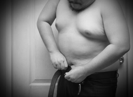 Overweight man trying to fasten too small jean pants.Black and white tone, Represent of fat, obesity, big belly. 版權商用圖片