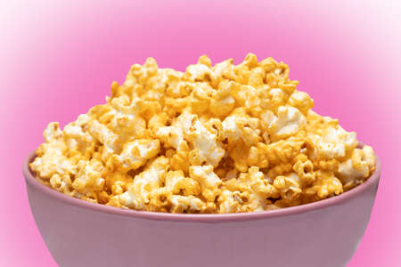 Popcorn in pink big bowl isolated on pink background. Unhealthy food concept. Health promotion concept.