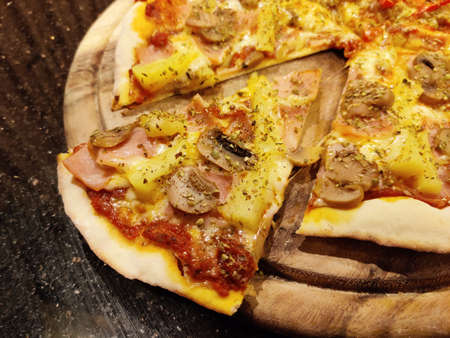Sliced hawaiian pizza, a pizza topped with tomato sauce, cheese, pineapple, mushroom and ham. serving on round wooden plate.