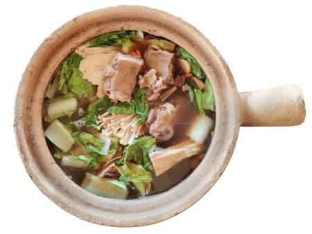 Bak kut teh serving in clay pot, a pork rib dish cooked in broth popularly served in Malaysia and Singapore isolated on white