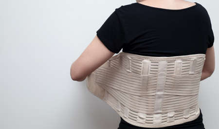 Woman in black t-shirt wearing back support belt for back pain and spinal support. Medical care concept