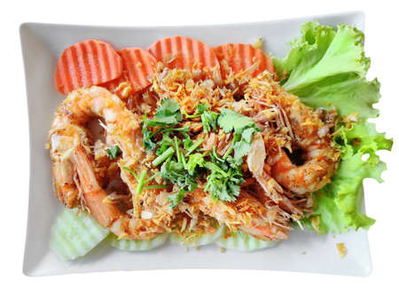 Stir Fried Shrimp with Garlic and Pepper, serving with fresh carrot and cucumber and sprinkle with coriander. Traditional Thai Food