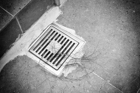 Hair loss clogging drain after bathing in restroom. Alopecia disorder or symptom of patients who got chemotherapy for cancer treatment. black and white tone