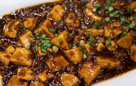 Closed up of Mapo tofu recipe, a popular Chinese dish consist of tofu set in a spicy saucei, along with minced meat, traditionally beef. serving on white plate.
