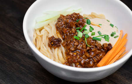 Sichuan Spicy Noodle with garlic chili oil and minced pork, serving on white bowl. Traditional food of Sichuan province. Chinese food concept.