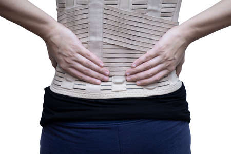 Woman in black t-shirt wearing back support belt for back pain and spinal support. Medical care concept. isolated on white background