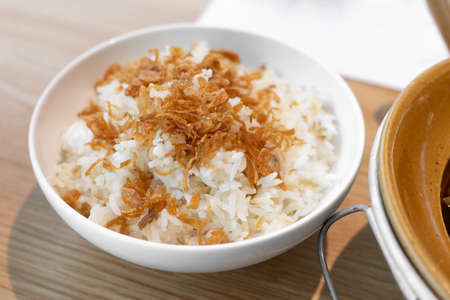 Steamed rice topped with fried shallots, serving on white bowl.