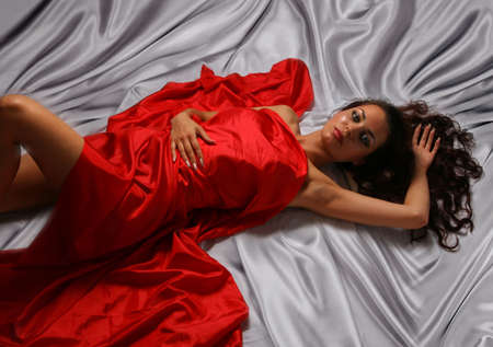Glamour Girl lyeing on the Light background in Red Silk