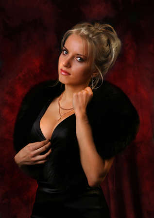 Beauty blonde girl in black dress with fur on the red backdrop