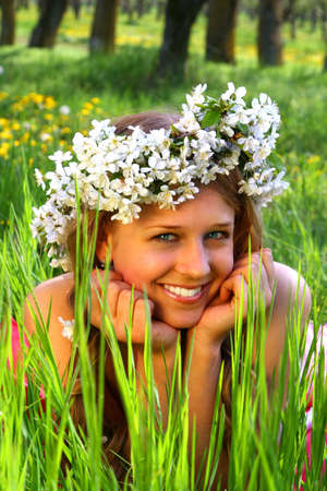 Girl with toothy smile lie in the grass with cherry blossoms Stock Photo